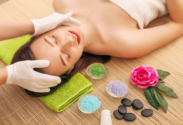 Primo piano di una giovane donna che ottiene trattamento della stazione termale al salone di bellezza. massaggio viso spa. trattamento di bellezza del viso. salone spa.