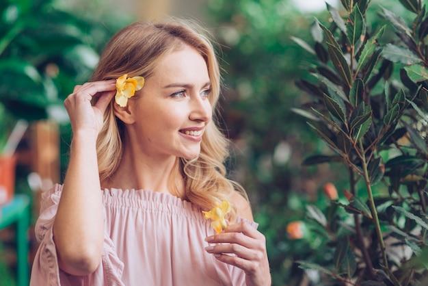 Primo piano di una giovane donna che pone il fiore giallo dietro il suo orecchio