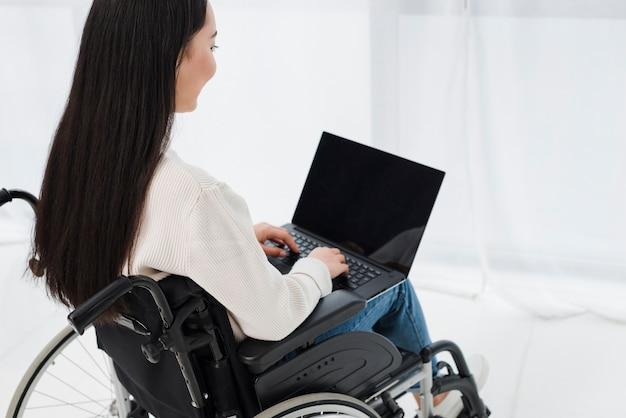 Primo piano di una giovane donna che si siede sulla sedia a rotelle con laptop