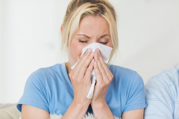 Primo piano di una giovane donna che soffre di raffreddore