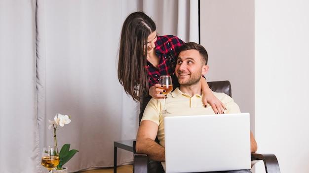 Primo piano di una giovane donna che tiene in mano bicchiere di vino in piedi dietro l'uomo con laptop