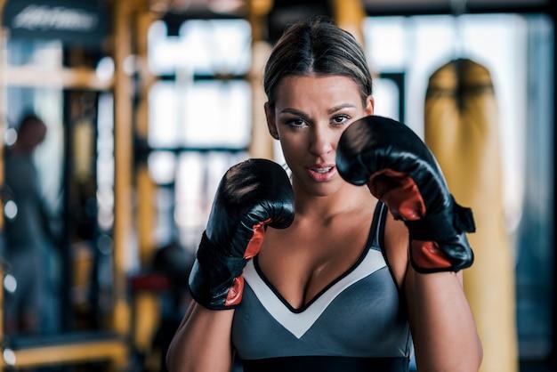 Primo piano di una giovane donna in forma in guantoni da boxe, vista frontale.