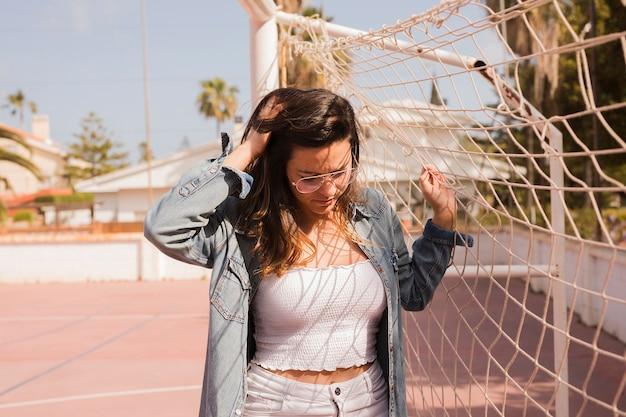 Primo piano di una giovane donna in piedi vicino alla rete di calcio