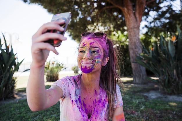 Primo piano di una giovane donna ricoperta di colore holi prendendo selfie sul cellulare