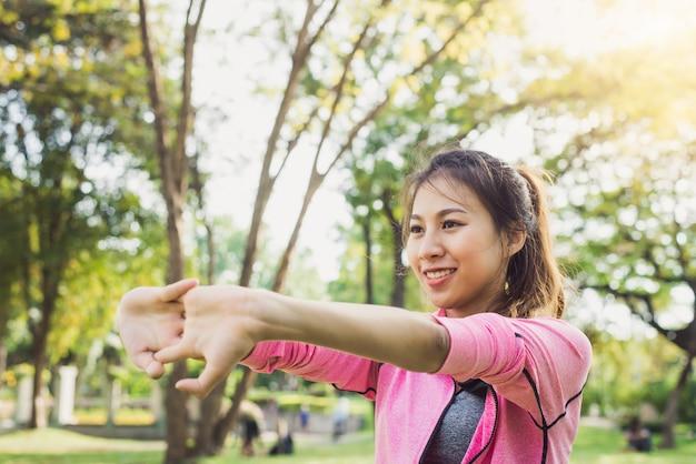 Primo piano di una giovane donna riscaldare il suo corpo allungando le braccia