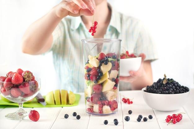 Primo piano di una giovane donna si prepara a frullare frutti e bacche