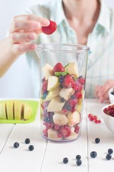 Primo piano di una giovane donna si prepara a frullare la frutta