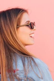 Primo piano di una giovane donna sorridente che indossa occhiali da sole su sfondo rosa