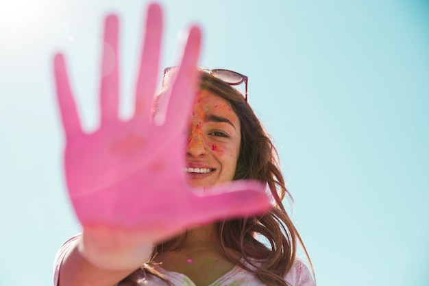 Primo piano di una giovane donna sorridente che mostra la sua mano rosa dipinta