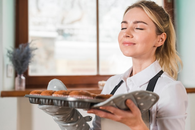 Primo piano di una giovane donna sorridente che odora i muffin al forno freschi