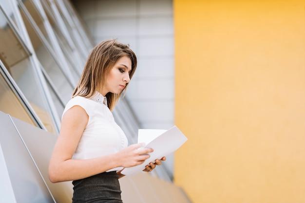 Primo piano di una giovane imprenditrice controllando i documenti cartacei
