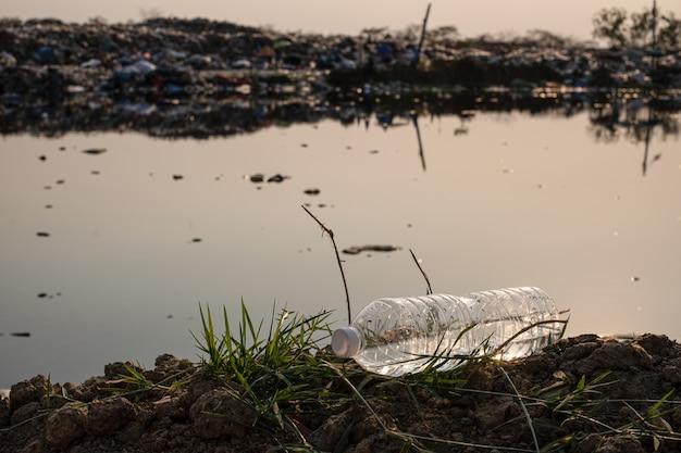 Primo piano di una goccia di bottiglia di plastica trasparente sul terreno con acqua inquinata e montagna grande immondizia sullo sfondo