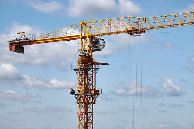Primo piano di una gru di costruzione gialla su una priorità bassa del cielo blu, fuoco selettivo