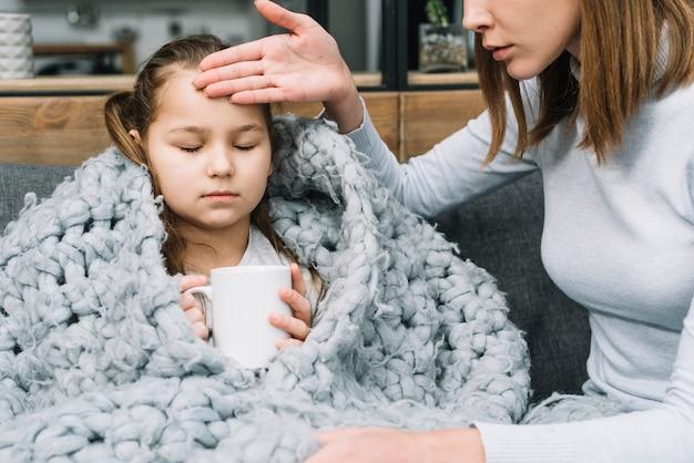 Primo piano di una madre che tocca la fronte di sua figlia che tiene tazza bianca
