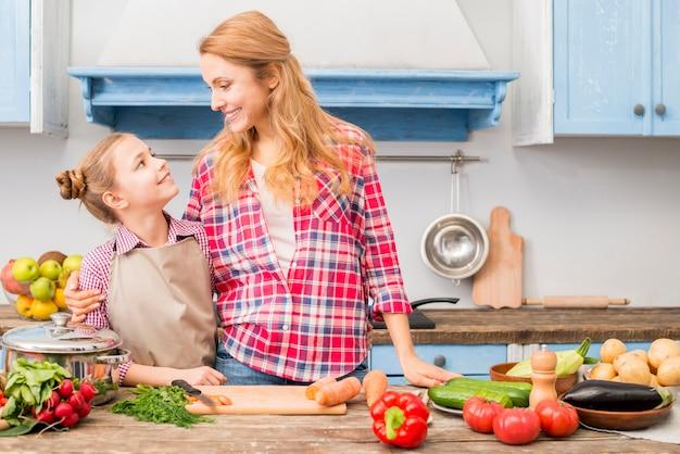 Primo piano di una madre e sua figlia guardando a vicenda in piedi davanti al tavolo con verdure colorate