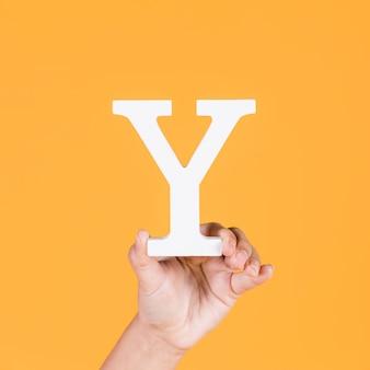 Primo piano di una mano che regge l'alfabeto y su sfondo