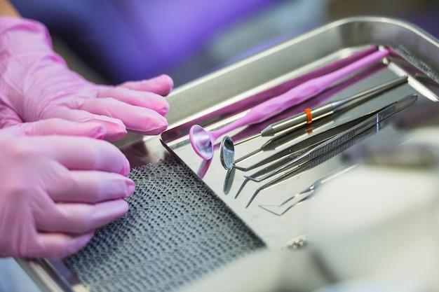 Primo piano di una mano del dentista vicino agli strumenti dentari sul vassoio