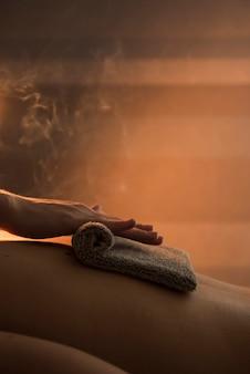 Primo piano di una mano del terapista che massaggia la parte posteriore della donna con l'asciugamano caldo in stazione termale