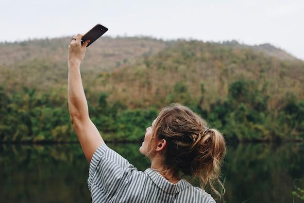Primo piano di una mano della donna che alza il suo smartphone su che prende una foto del concep di viaggio e di turismo della natura