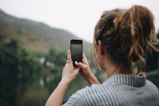 Primo piano di una mano della donna che alza il suo smartphone su che prende una foto della natura