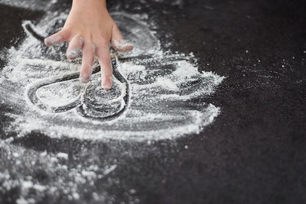 Primo piano di una mano della ragazza che disegna heartshape in farina