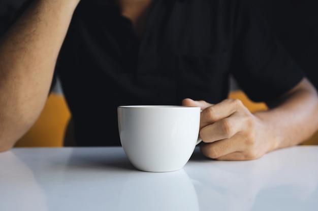 Primo piano di una mano di un uomo d'affari che tiene una tazza di caffè
