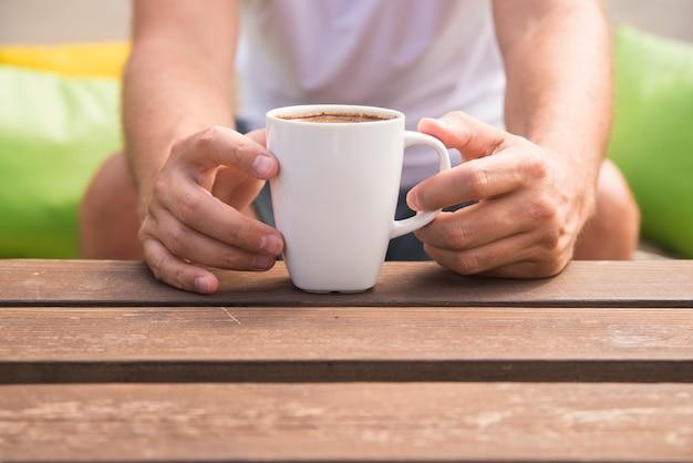 Primo piano di una mano di un uomo in possesso di una tazza di caffè con uno sfondo verde all'esterno