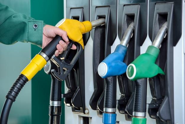 Primo piano di una mano di uomo usando un ugello di carburante in una stazione di benzina.