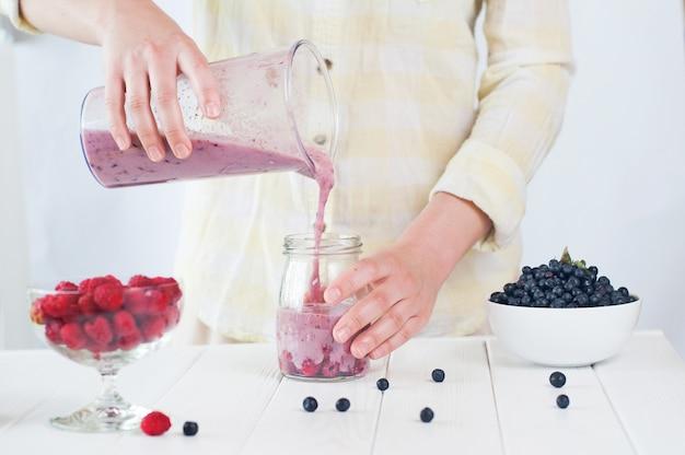 Primo piano di una mano femminile miscelazione di frutti e bacche