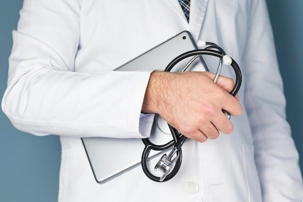 Primo piano di una mano maschio di medico che tiene compressa digitale e stetoscopio