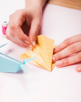 Primo piano di una mano umana che fa uccello di origami
