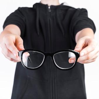 Primo piano di una mano umana che tiene gli occhiali