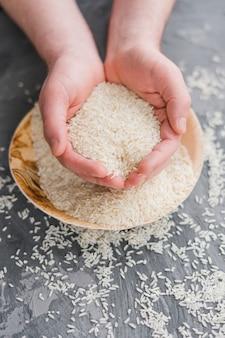 Primo piano di una mano umana che tiene i grani di riso bianco crudo al gelsomino