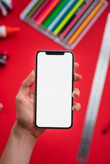 Primo piano di una mano umana che tiene smartphone con display bianco vuoto su sfondo sfocato