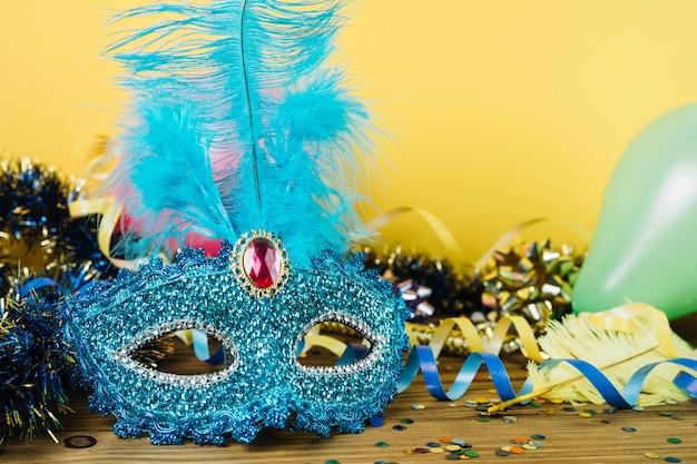 Primo piano di una maschera di carnevale veneziano blu con piuma e materiale di decorazione del partito