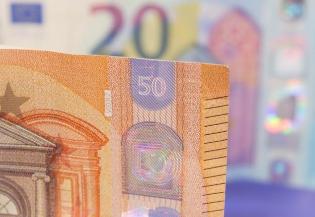 Primo piano di una nuova banconota di cinquanta euro con un'altra banconota da venti, sfuocato sullo sfondo.