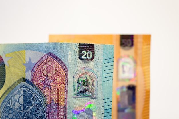 Primo piano di una nuova banconota di venti euro con un'altra banconota da cinquanta, sfuocato sullo sfondo.