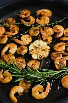 Primo piano di una padella con gamberoni fritti e rametti di rosmarino e timo.