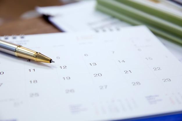 Primo piano di una penna e calendario sulla scrivania.