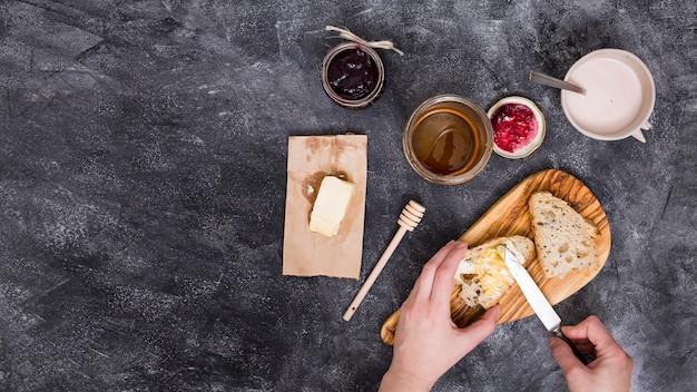 Primo piano di una persona che aggiunge il burro con il coltello; marmellata di lamponi e miele su sfondo nero strutturato