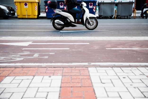 Primo piano di una persona che guida la bici sulla strada