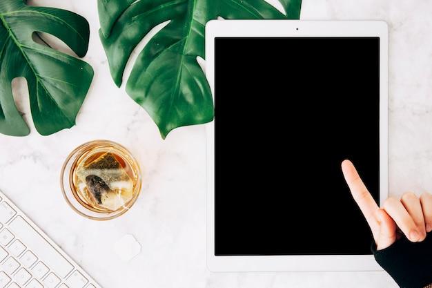Primo piano di una persona che punta il dito sopra la tavoletta digitale con un bicchiere di tè sul marmo con texture di sfondo