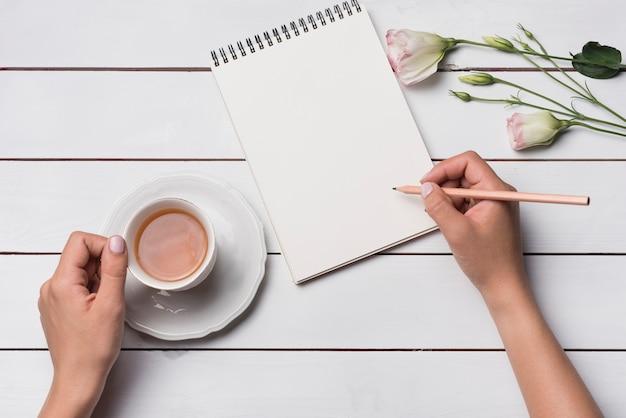 Primo piano di una persona che scrive sul blocco note con la tazza di tettarella sulla scrivania in legno