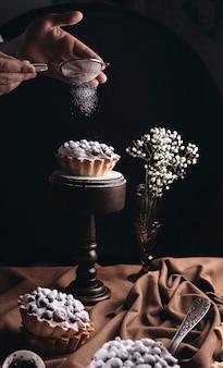 Primo piano di una persona che spolvera la polvere dello zucchero sulla torta di frutta con il vaso di fiori del respiro del bambino