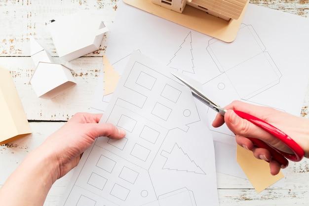 Primo piano di una persona che taglia il disegno della casa con le forbici