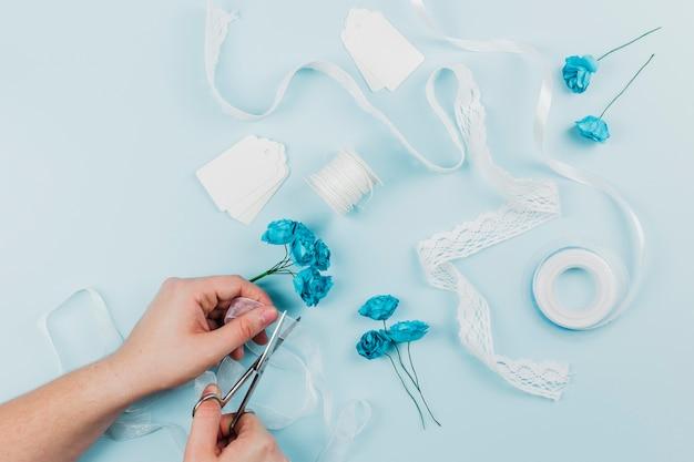 Primo piano di una persona che taglia il nastro con le forbici per legare le rose blu su sfondo colorato