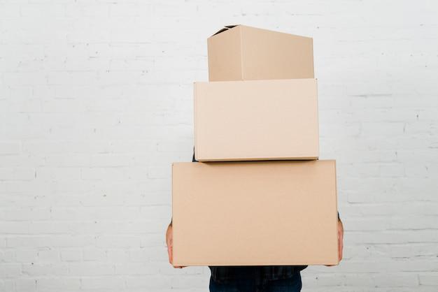 Primo piano di una pila della tenuta della persona di scatole di cartone contro la parete dipinta bianca