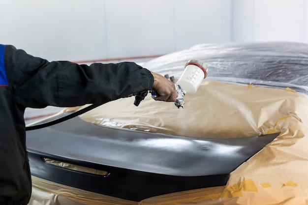 Primo piano di una pistola a spruzzo con vernice nera per dipingere un'auto in una cabina speciale