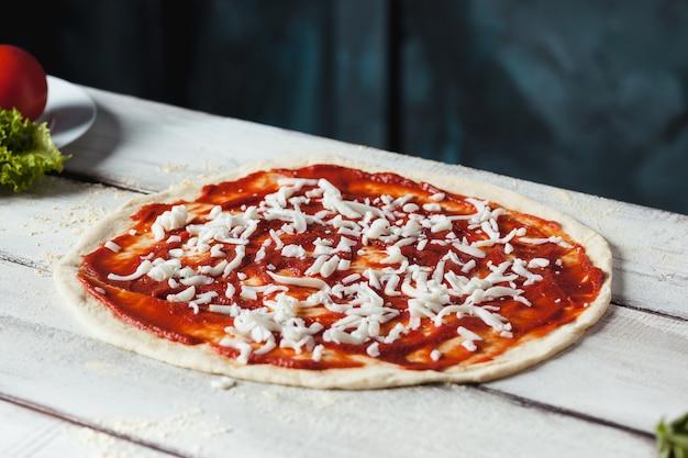 Primo piano di una pizza cruda fatta in casa con formaggio e salsa di pomodoro su un fondo di legno