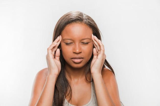 Primo piano di una ragazza adolescente africana che soffre di mal di testa